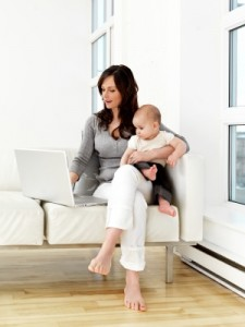 woman with computer holding a baby