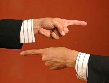 two hands of businessmen, fingers pointing at each other