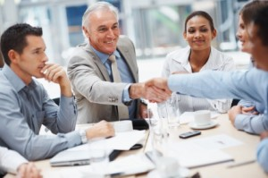 Teamwork: Senior business man shaking a team member's hand during a meeting