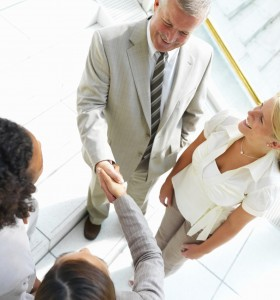Business colleagues shaking hands in office
